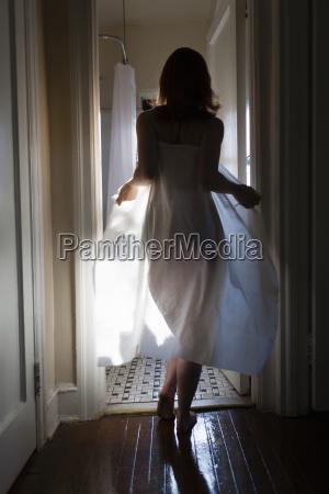 mid adult woman walking towards bathroom