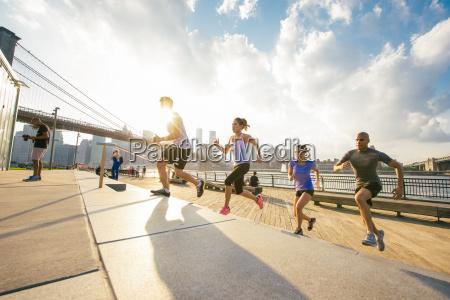 four running friends running up riverside