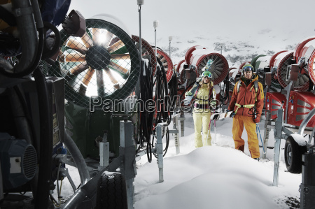 young people standing among snowmobiles