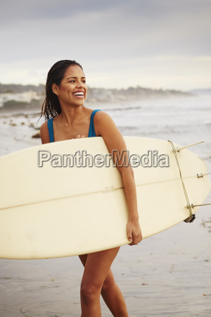 young woman strolling on beach carrying