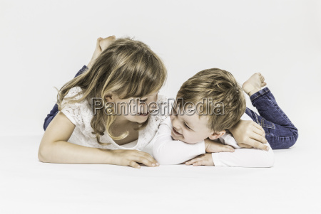brother and sister lying on stomach