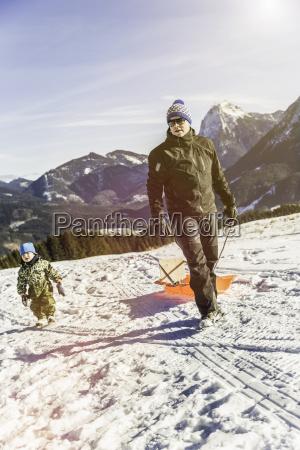 mann zieht schlitten auf schnee achenkirch