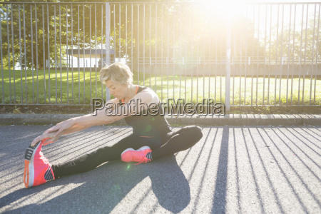 mature woman running stretching outdoors