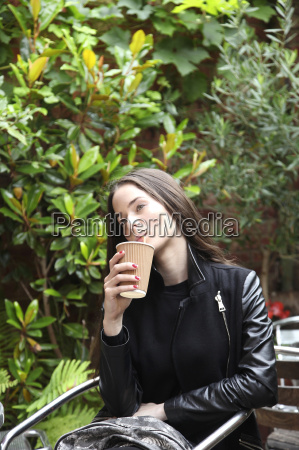 young woman holding disposable cup drinking