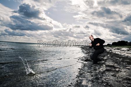 man throwing stone in ocean koge