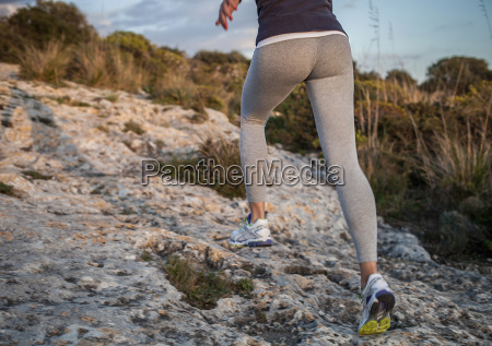 young woman running uphill rear view