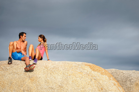 couple sitting on boulder