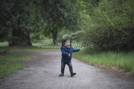 female toddler walking on forest path
