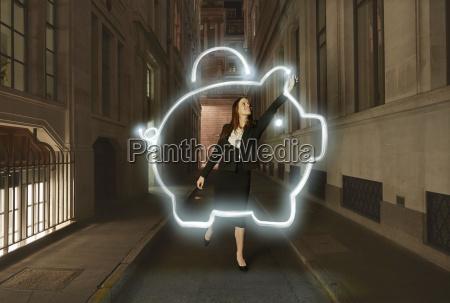 businesswoman light painting glowing piggy bank