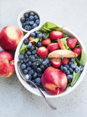 still life of blueberries strawberries peaches