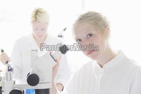 scientist at microscope in lab