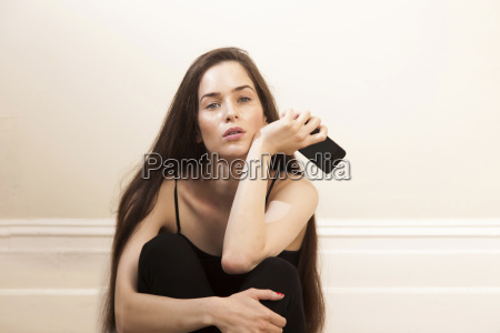 young woman holding smartphone sitting hugging