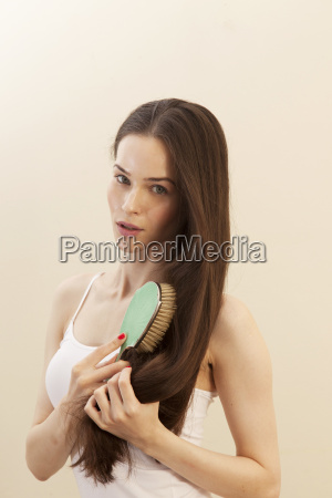 portrait of young woman brushing hair