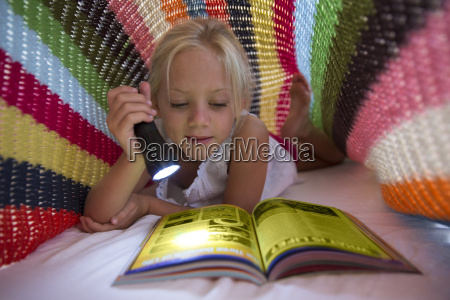 girl lying on bed hiding under