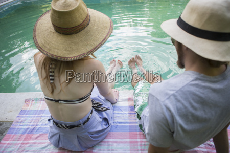 couple on sarong dipping legs into