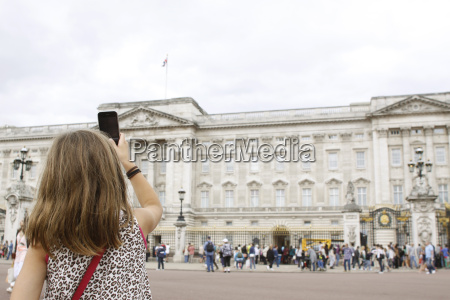 young girl taking picture of buckingham
