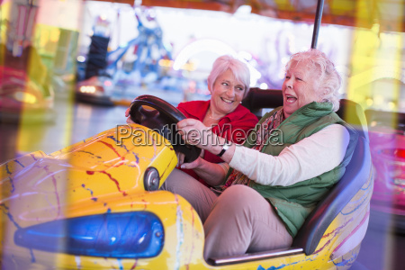 two senior women driving bumper car