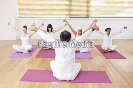 people practicing yoga together in class