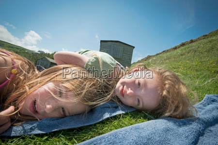 girls laying on towels in grass