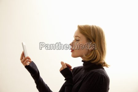 woman reading message on cellular phone