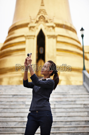 woman taking pictures at ornate temple