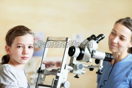 optometrist preparing to examine girls eyes