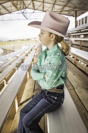 girl wearing cowboy hat on bench