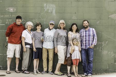 familie mit drei generationen vor wand