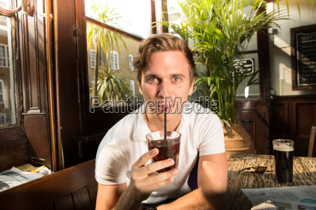 portrait of young man drinking through