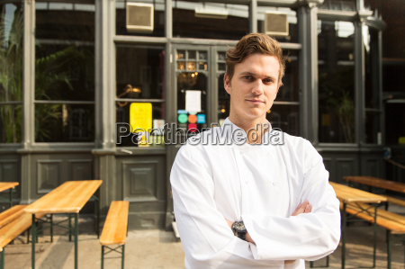 young chef standing outside of work