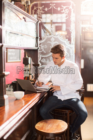 young chef sitting on bar stool