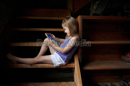 little girl sitting on basement steps
