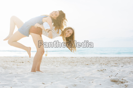 two young female friends giving back