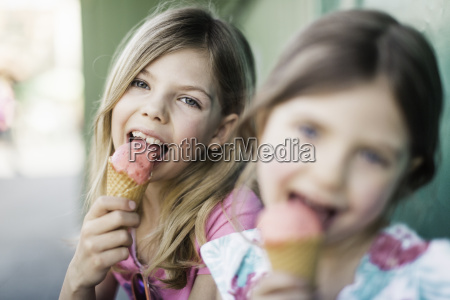 two young girls eating icecream