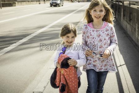 two young girls walking down street