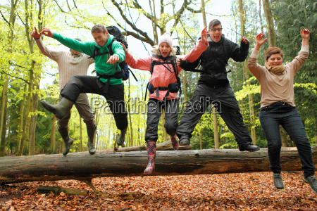 friends jumping off log in forest