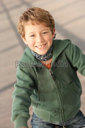 smiling boy standing on city street