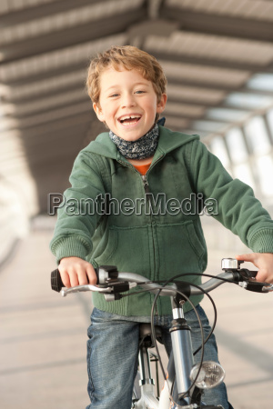 boy riding bicycle in city tunnel