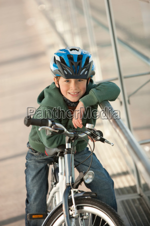 boy sitting on bicycle in city