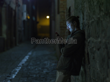 young man in street leaning against