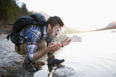 young man hiking crouching by lake