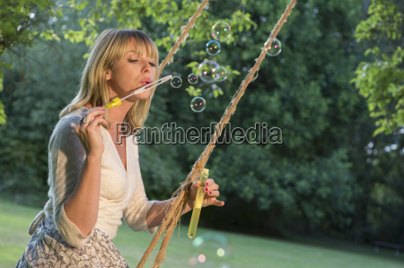 woman on swing blowing soap bubbles