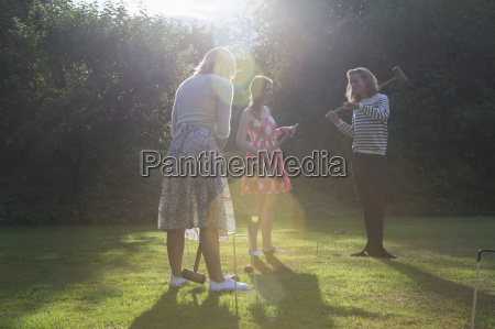 friends playing croquet in garden