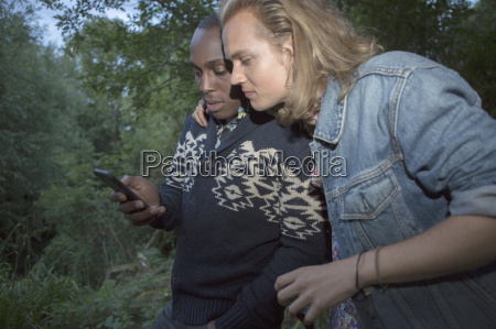 two friends sharing message on smartphone