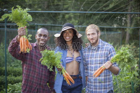 friends holding carrots from allotment