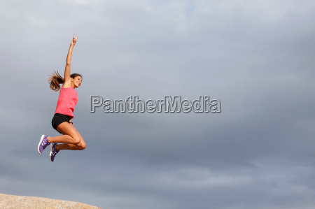 woman jumping for joy on boulder