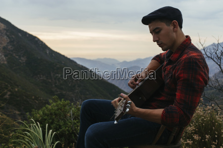 young man sitting in mountain landscape