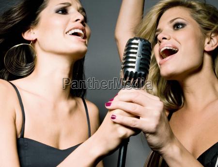 two women singing into mic