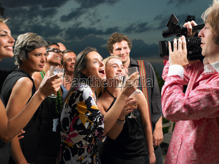 man filming people at a cocktail