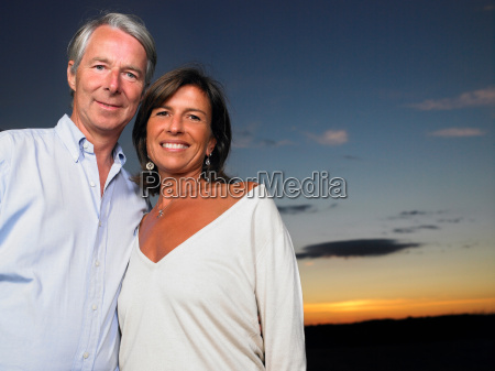 couple in a field sunset
